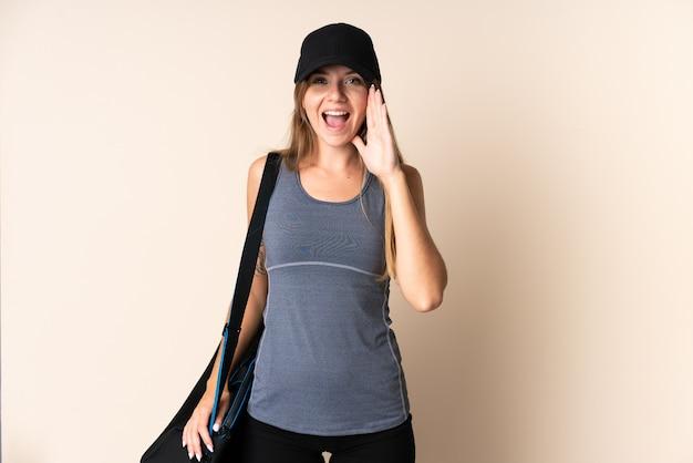 Jovem esportiva lituana segurando uma sacola esportiva isolada em bege, gritando com a boca aberta