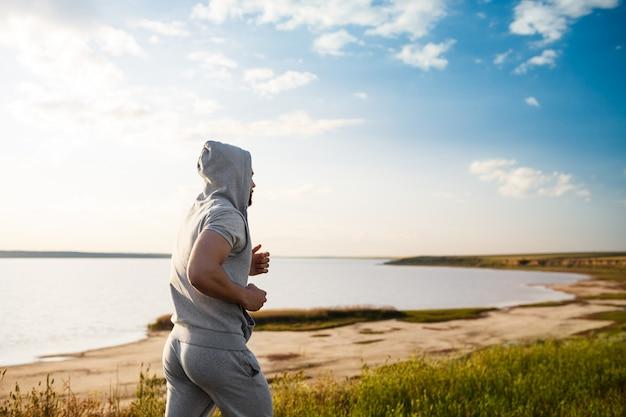 Jovem esportiva, movimentando-se em campo ao nascer do sol.
