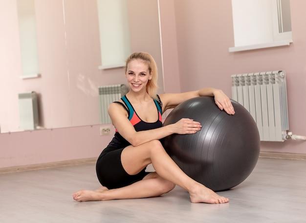 Jovem esportiva na academia com uma bola de fitness