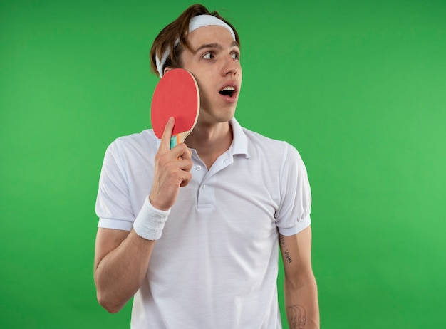 Jovem esportivo surpreso olhando para o lado usando bandana e pulseira, colocando raquete de pingue-pongue no rosto isolado na parede verde