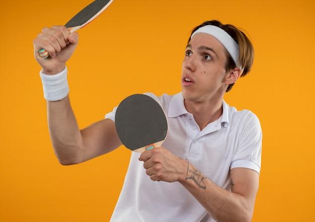 Jovem esportivo surpreso olhando para o lado usando bandana e pulseira levantando raquetes de pingue-pongue isoladas na parede laranja