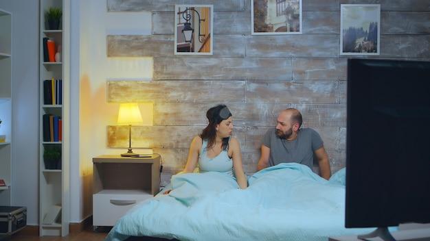 Jovem esposa acordando o marido após ter um pesadelo enquanto dormia.