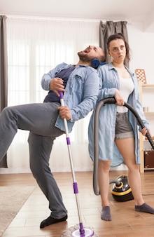 Jovem esposa irritada porque seu marido alegre não a deixa limpar a casa
