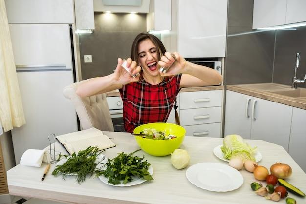 Jovem esposa preparando salada com legumes, adicione sal e pimenta para melhor sabor.