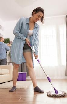 Jovem esposa rindo enquanto esfrega o chão