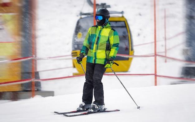 Jovem esquiador descendo a encosta durante uma tempestade de neve