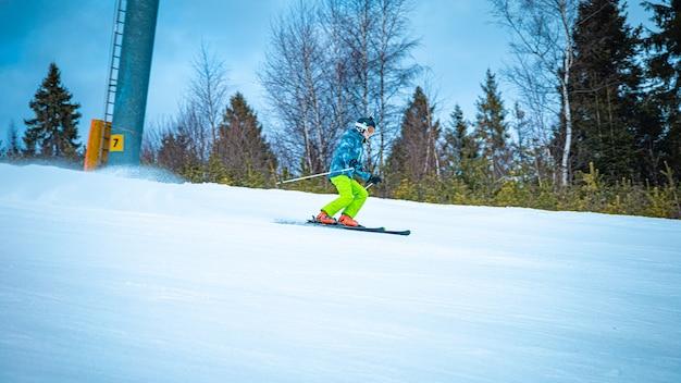 Jovem esquiador descendo rapidamente a encosta