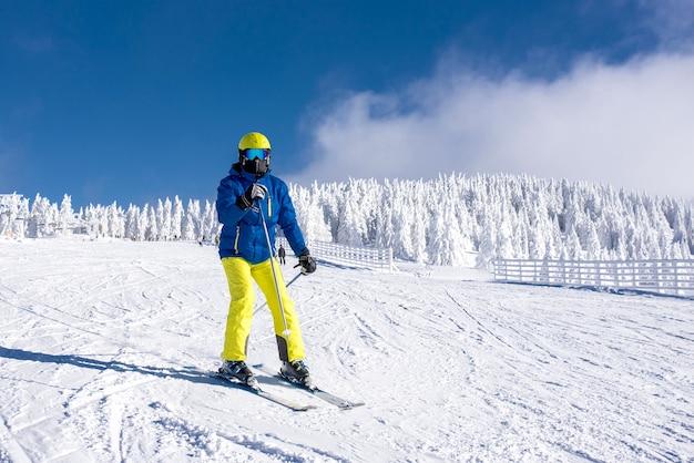 Jovem esquiador em movimento com uma bela paisagem de inverno