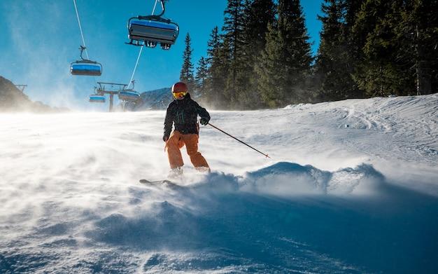 Jovem esquiador fazendo curvas durante condições de vento na encosta