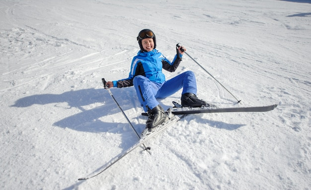 Jovem esquiador feminino após a queda na encosta da montanha