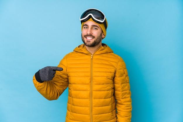 Jovem esquiador homem caucasiano isolado pessoa apontando com a mão para um espaço de cópia de camisa, orgulhoso e confiante