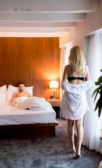 Jovem está à espera de uma mulher sexy na cama
