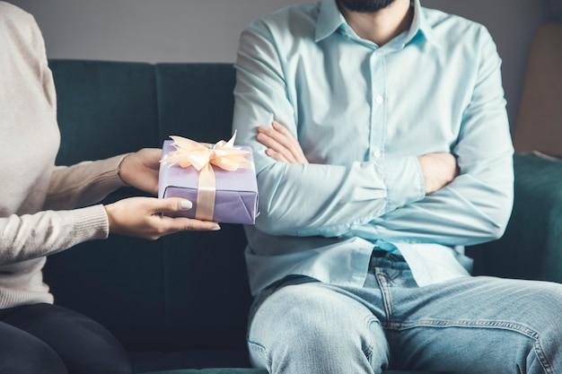 Jovem está dando um presente para um homem ofendido