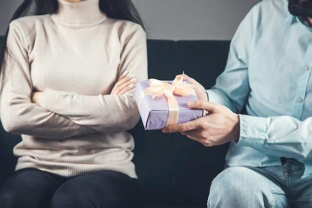 Jovem está dando um presente para uma mulher ofendida