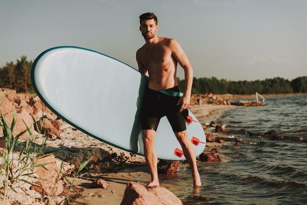 Jovem está de pé na praia com surf
