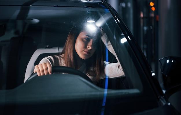 Jovem está dentro de um automóvel moderno novo.