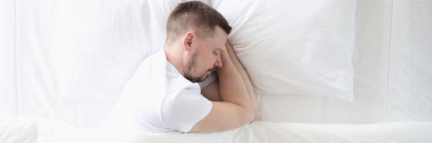 Jovem está dormindo pacificamente em uma grande cama branca conceito de sono saudável