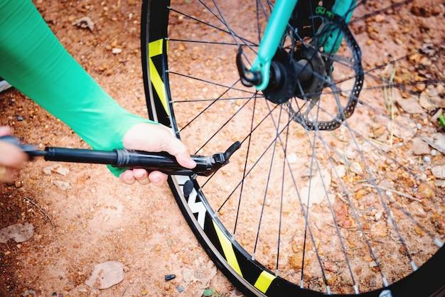 Jovem está enchendo a roda da bicicleta com ar