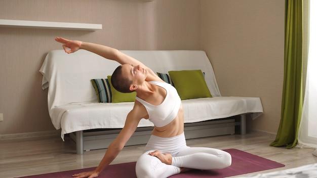 Jovem está envolvida em fitness em casa durante um período de auto-isolamento. o conceito de um estilo de vida saudável