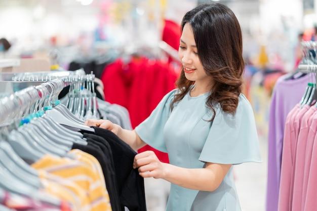 Jovem está escolhendo comprar roupas no shopping