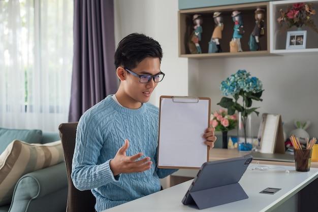 Jovem está estudando online em casa usando um laptop. documento de aprendizagem.