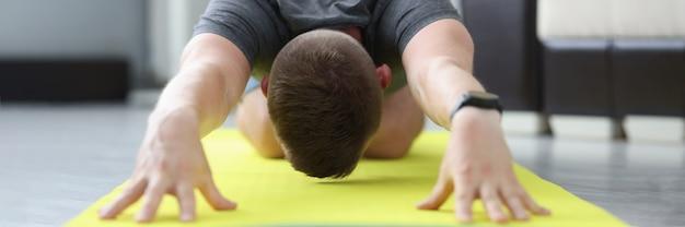 Jovem está fazendo exercícios para alongar os músculos das costas