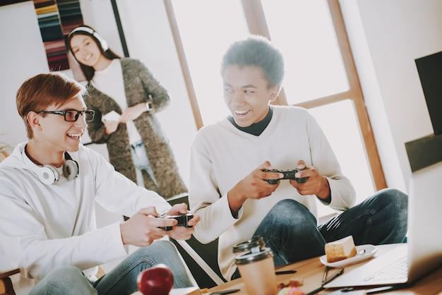 Jovem está jogando no videogame com o amigo.