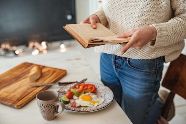 Jovem está lendo um livro antigo no café da manhã. mãos de close-up e configuração de mesa de jantar. estilo sertanejo. ovos mexidos e vegetais frescos e lendo um livro interessante pela manhã