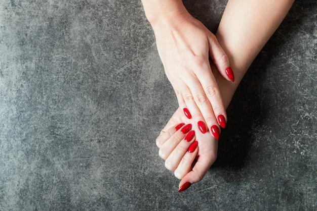 Jovem está mostrando suas unhas vermelhas manicure