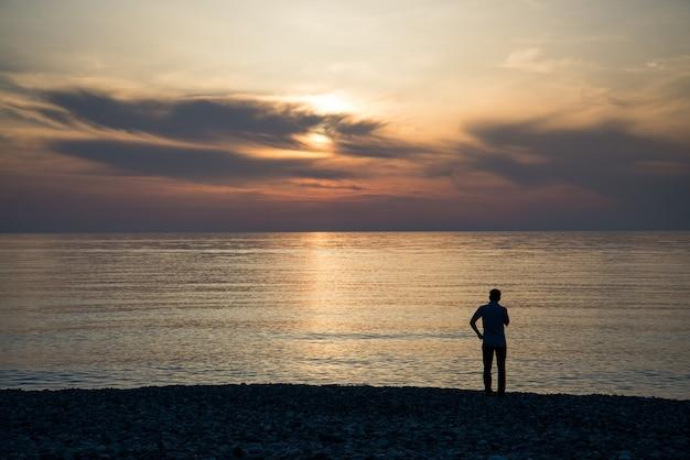 Jovem está olhando para o nascer do sol.