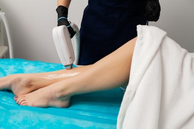 Jovem está recebendo depilação a laser para pernas no salão de beleza