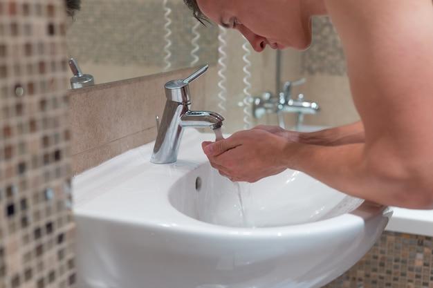 Jovem está se lavando no banheiro de manhã antes do início do dia de trabalho