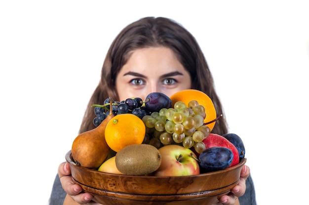 Jovem está segurando um vaso de madeira com frutas nas mãos. uva, laranja, maçã, pêra, kiwi e outros