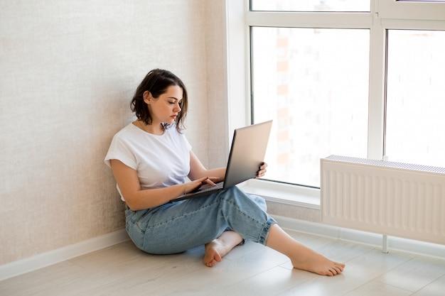 Jovem está sentada no chão com um laptop em casa, ao lado de uma janela panorâmica