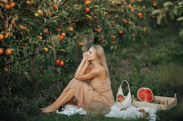 Jovem está sentada sobre um cobertor branco do lado de fora no pomar de maçãs. mulher feliz fazendo piquenique no jardim de outono com melancia, maçãs e uvas