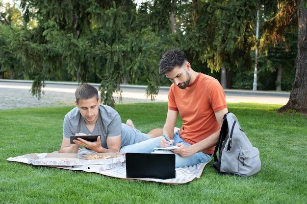 Jovem está sentado com um laptop e tablet na grama em um campus universitário e fazendo anotações no caderno.