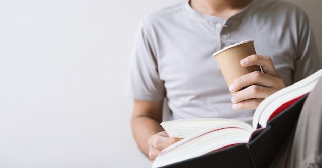 Jovem está sentado lendo um livro enquanto segura uma xícara de café no quarto