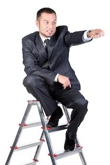 Jovem está sentado na escada e aponta em algum lugar.