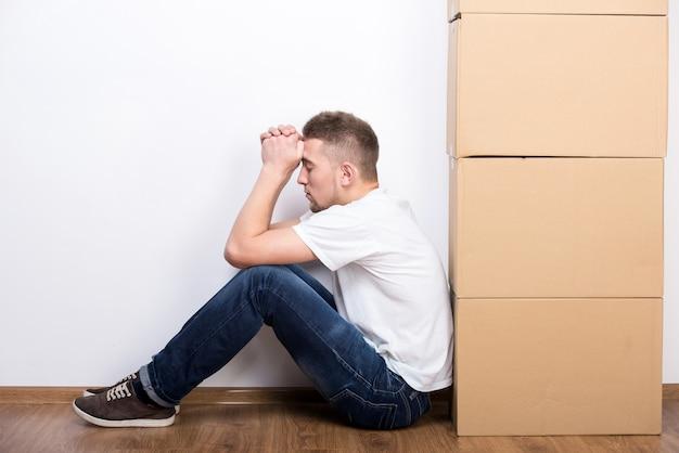 Jovem está sentado no chão ao lado de caixas de papelão.