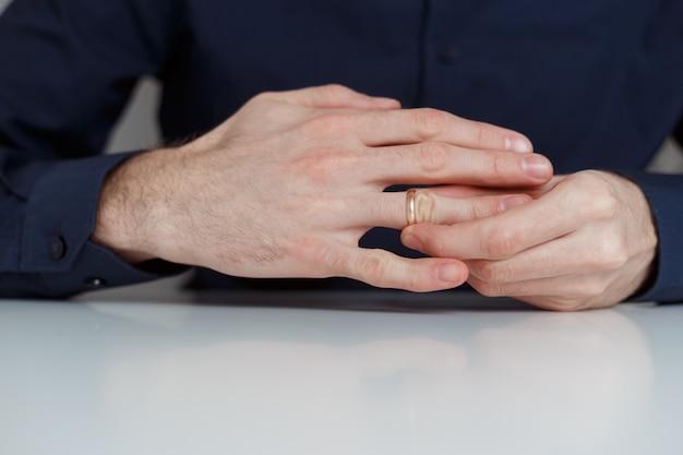 Jovem está tirando o anel de casamento.