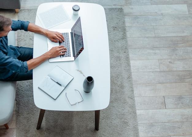 Jovem está trabalhando em um laptop em seu apartamento pessoas e tecnologia
