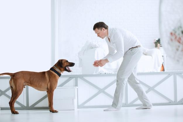 Jovem está treinando seu cachorro em seu apartamento