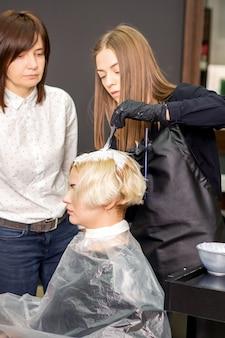 Jovem estagiária aprende a desenhar cabelos femininos sob supervisão de um cabeleireiro profissional em uma barbearia