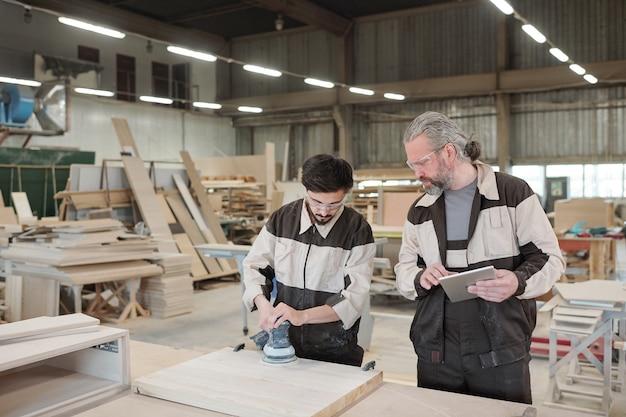 Jovem estagiário em vestuário de trabalho e óculos de proteção, moendo a superfície de uma peça de madeira com o mestre sênior por perto