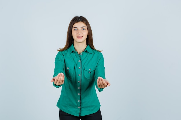 Jovem, estendendo as mãos em concha na blusa verde, calça preta e parecendo feliz, vista frontal.