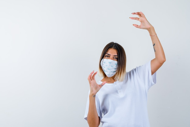 Jovem, esticando a mão como segurando algo imaginário em uma camiseta branca e uma máscara e parece confiante. vista frontal.