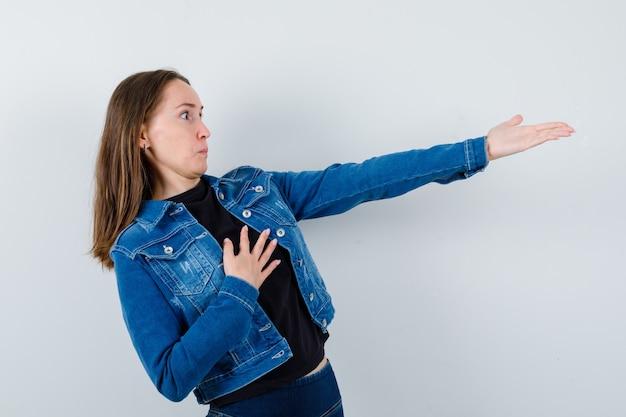 Jovem, esticando a mão para mostrar algo na blusa, jaqueta e parecendo surpresa. vista frontal.