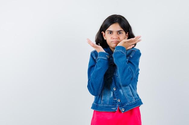 Jovem, esticando as mãos de forma questionadora em camiseta vermelha e jaqueta jeans e olhando perplexa, vista frontal.