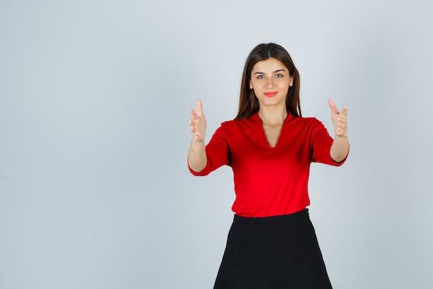 Jovem esticando as mãos mostrando a largura em uma blusa vermelha, saia preta e parecendo feliz