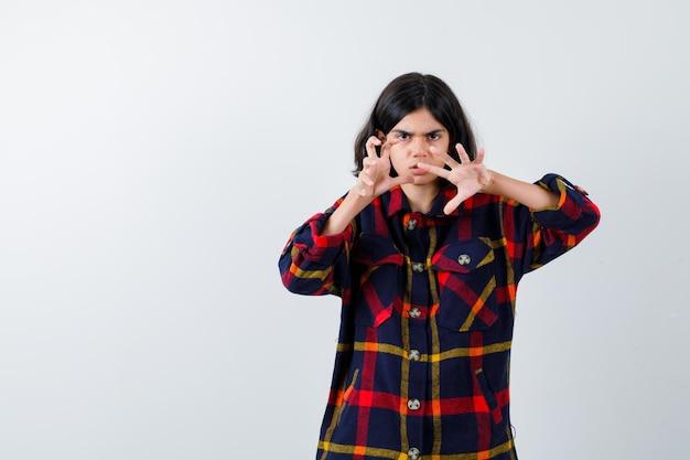 Jovem, esticando as mãos para ameaçar alguém de camisa xadrez e olhando furiosa, vista frontal.
